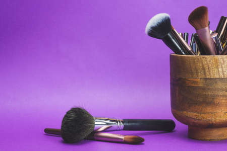Makeup brushes in wooden vase on purple background. various cosmetic brushes close up. skin care accessories
