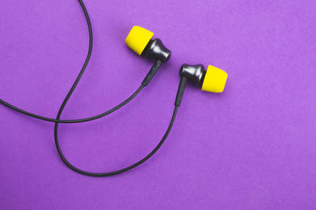 Earphones with yellow ear cushions on a purple background. in-ear headphones. audio equipment