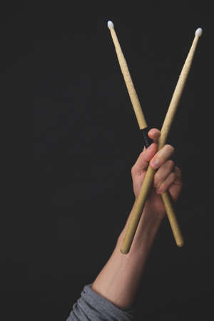Hand holds wooden drumsticks in the dark. copy space