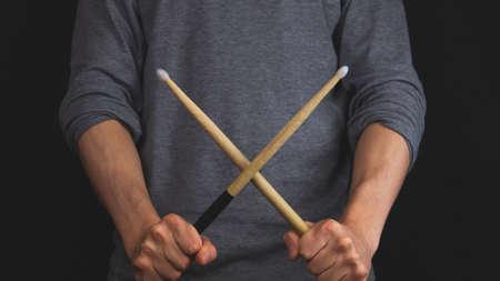 Hands holds crossed wooden drumsticks in the dark