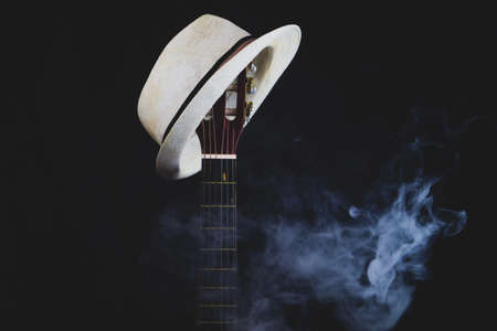White hat hangs on the smoking guitar fretboard. acoustic musical instrument. strings on the guitar neck close up Stock Photo