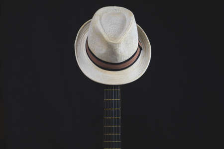 White hat hangs on the guitar fretboard. acoustic musical instrument. strings on the guitar neck close up 版權商用圖片