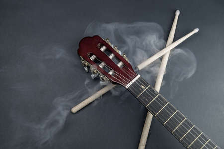 Drumsticks and guitar fretboard in smoke. acoustic musical instrument. copy space Stock Photo