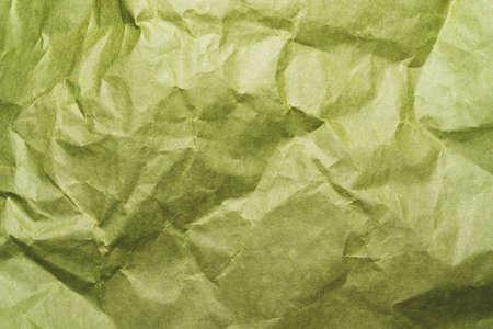 Crumpled green paper close up. creased kraft paper material