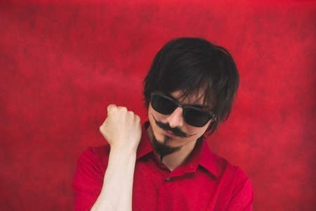 Young man with sunglasses in red shirt on the red background. male portrait