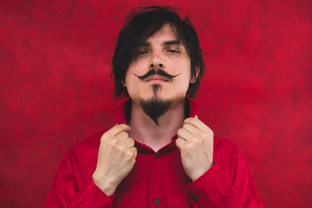 Male portrait. young man in red shirt on the red background Stock Photo