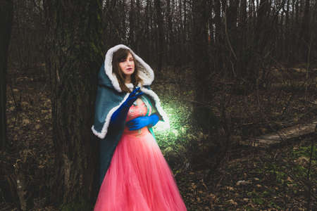 Sorceress casting a spell. woman in fantasy costume with cape leaned against a tree. magic autumn Stock Photo