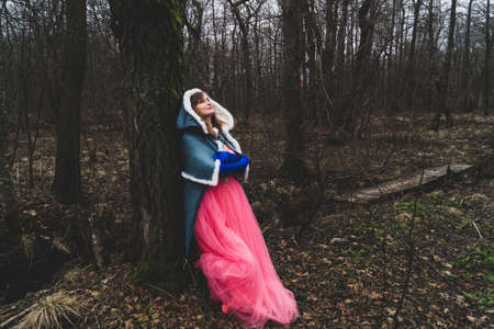 Woman with mantle leaned against a tree. adult woman in fantasy costume with cape. magic autumn
