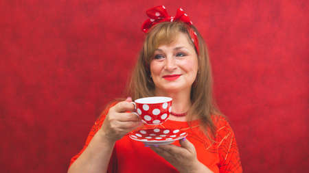 Woman in red posing on the red background. spotted cup with saucer in the hands. funny style Stock Photo