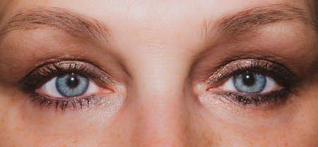 Female eyes. freckles skin. mascara on the eyelashes. iris close up