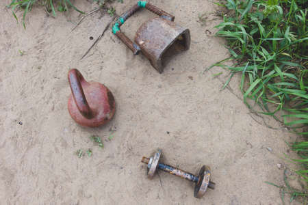 Kettlebells and dumbbell on the sand. handmade fitness equipment. weight lifting