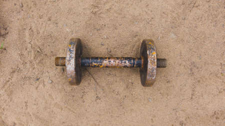 Dumbbell on the sand. handmade fitness equipment. weight lifting