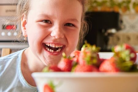 Beautiful European child in the kitchen eating strawberries and drinking milk.