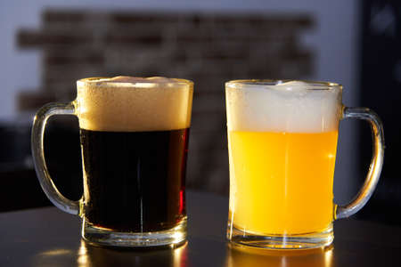 two mugs of dark and light beer on the bar. International beer day. Culture of brewing in a craft beer store