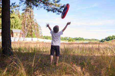 a boy plays in nature throwing an inflatable circle up. Concept of outdoor recreation with children. Healthy lifestyle 版權商用圖片