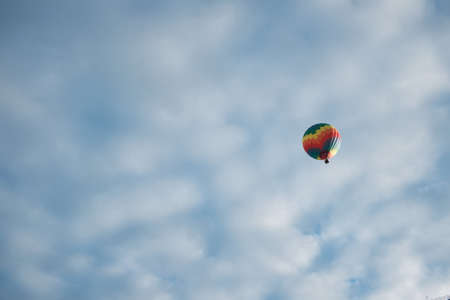 one multicolored balloon flies high in the sky covered with clouds Banco de Imagens
