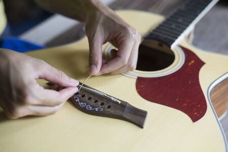 Change the acoustic guitar strings, Step to insert guitar string into the hole, Close-up