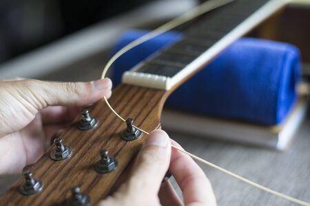 Checking the acoustic guitar string, Expert is tuning the guitar string, Close-up Stock fotó
