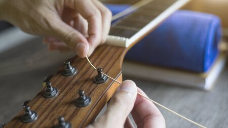 Checking the acoustic guitar string, Expert is tuning the guitar string, Close-up Banco de Imagens
