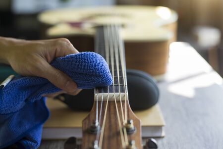 Guitar repairer is cleaning acoustic guitar, Clean cloth to wipe the fretboard, Close-up Banco de Imagens