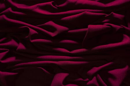 Dark pink wrinkled fabric, With lights falling into patterns, Art background caused by fabric. Reklamní fotografie