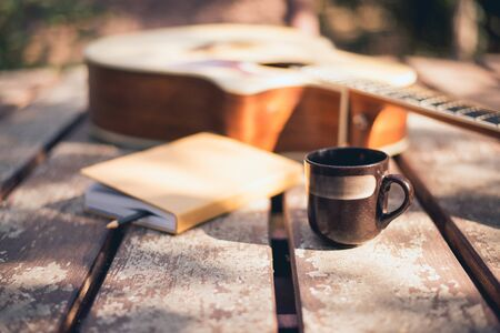 Composer's desk in nature, Coffee cup, notebook, and acoustic guitar placed, Close-up.