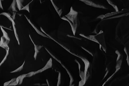 Crumpled cloth in black, Light causes patterns. 版權商用圖片
