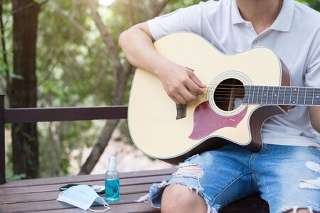 Hobbies during quarantine, Acoustic guitarist in garden at home, Copy-space.