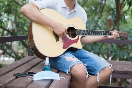 Hobbies during quarantine, Acoustic guitarist in garden at home, Mental health care. Stock Photo