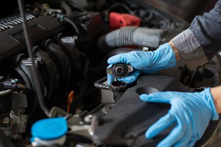Vérification du moteur, mécanicien vérifiant le radiateur de la voiture, gros plan.