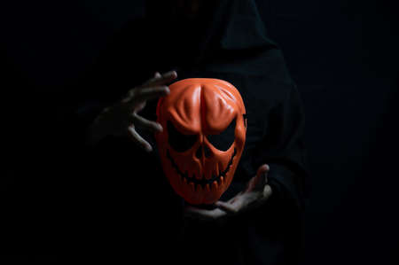Dark Halloween Concept, Orange ghost mask in hands of devil.