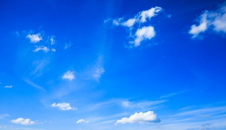 some: Some small white clouds spreaded over a bright blue sky