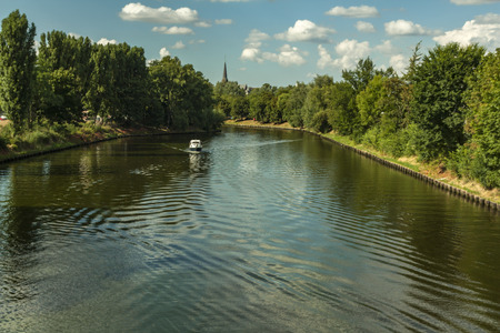 holydays: boattrip on an sunny day with a church spire in the backround and on both side of the river are green trees