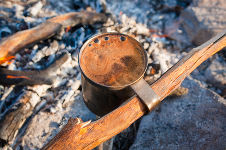 Cup of fragrant coffee with foam on a campfire, tourist morning outdoor.