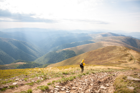 Mountain hiking tourism. Woman hiker  summer day in a beautiful landscape alone. Relaxation and solitude, active lifestyle Reklamní fotografie