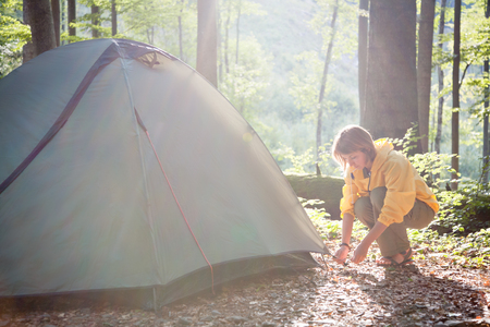 Tourism concept. Camping and hiking.  Woman setting tent in the