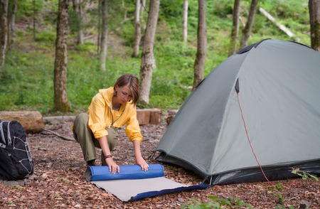 Tourism concept. Camping and hiking. Woman setting tent in the forest summer day Reklamní fotografie