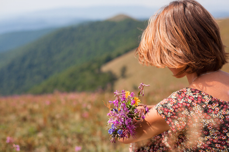 woman in summer dress with flowers enjoying mountain view. vacation and relaxation, silence