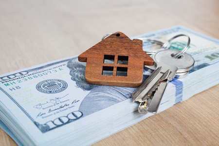 Real estate investing concept. American dollar, cash or housing. Keys close-up