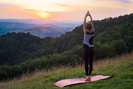 A woman doing yoga in the mountains at dawn. Morning summer meditation
