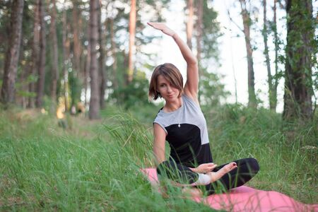 Woman practicing yoga alone in the forest outdoor. Morning summer meditation Reklamní fotografie