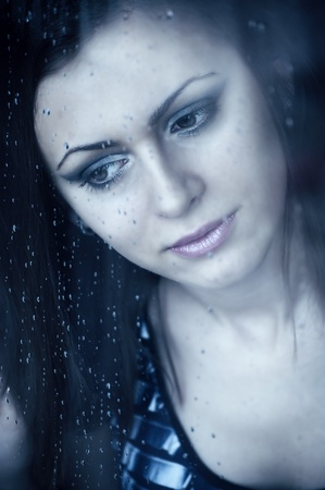 Young girl watching through the window, after a rain. Portrait. photo