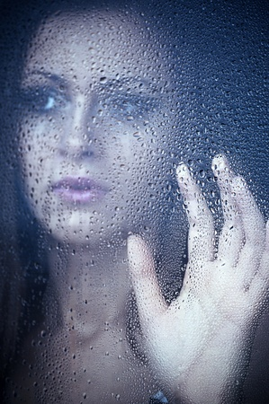 a girl watching through the window after a rain. Portrait. photo