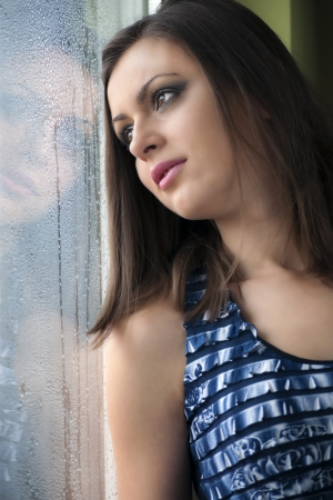 Beautiful girl watching through a wet window. Portrait Stock Photo - 12042808