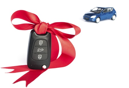 Gift car concept with red Bow and car key on focus