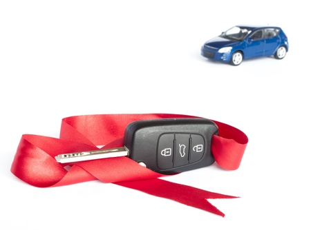 Gift car concept with red Bow and a blue car in the background. photo