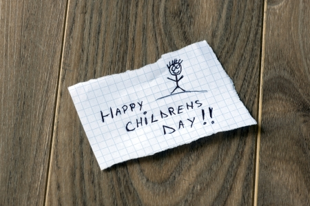 Happy Childrens Day - Kid writing with a smile man on wood background photo