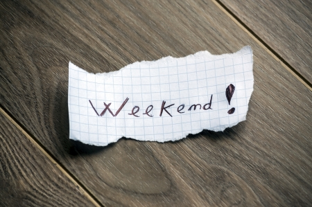 Weekend - Hand writing text on a piece of paper on wood background photo