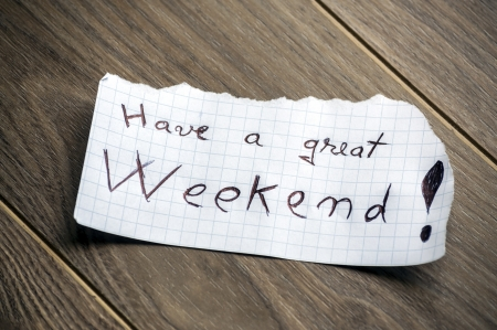 we: Have a great Weekend - Hand writing text on a piece of paper on wood background Stock Photo