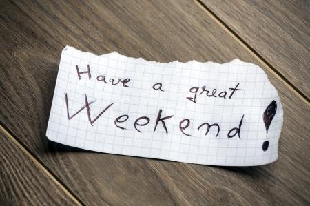 fin de semana: Que tengan un buen fin de semana - El texto escrito a mano en un pedazo de papel en el fondo de madera